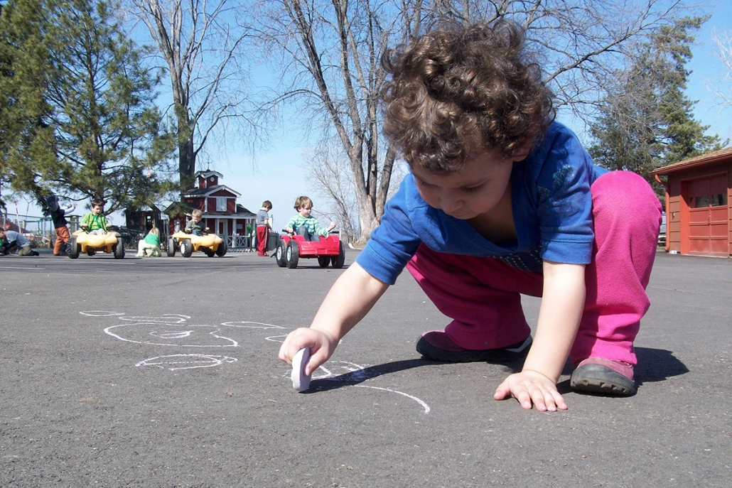 Child Drawing on Pavement with Chalk